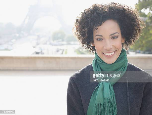 Woman outdoors by Eiffel Tower looking at camera