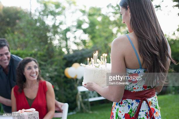 Woman outdoors carrying a birthday cake to a smiling couple