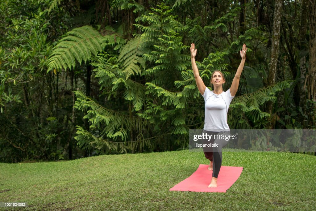 Woman outdoors doing yoga and relaxing : Stock Photo