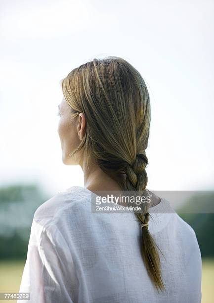 Woman outdoors, hair braided, rear view