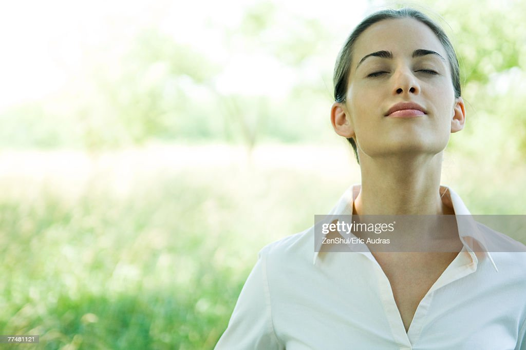 Woman outdoors, head and shoulders, head back and eyes closed : Stock Photo