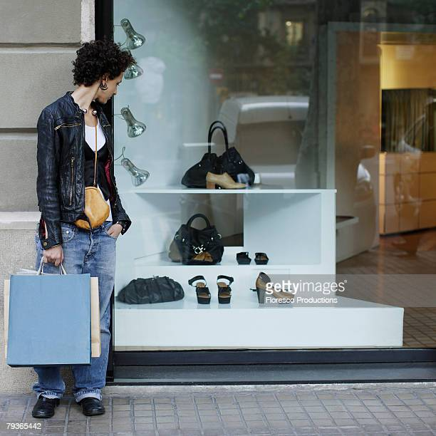 Woman outdoors holding shopping bags and window shopping