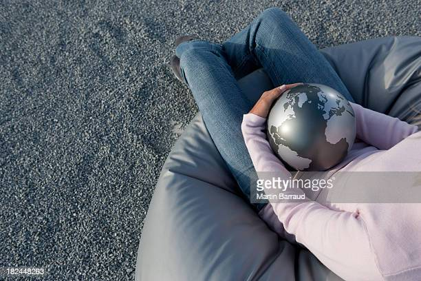 woman outdoors in beanbag chair holding globe - world kindness day stock photos and pictures