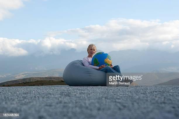 woman outdoors in beanbag chair holding globe - alleen één mid volwassen vrouw stockfoto's en -beelden