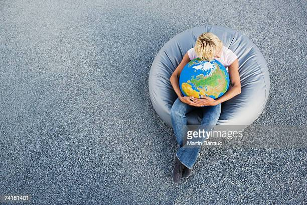 Woman outdoors in beanbag chair holding globe