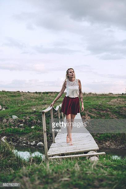 Woman outdoors in summer walking over old bridge