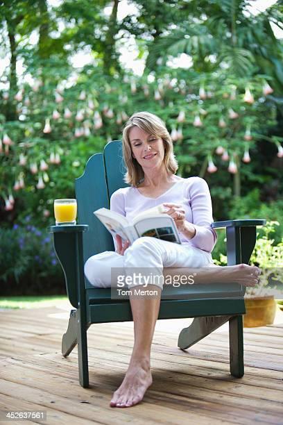 Frau im Freien im Hof sitzt auf einem Stuhl mit Buch