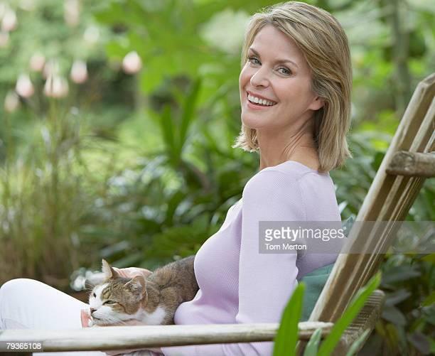 Frau im Freien im Hof mit Katze auf Ihrem Schoß