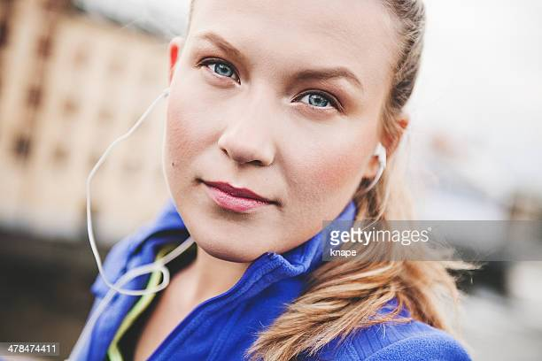 女性の音楽を聞きながら屋外で earbuds