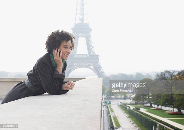 woman outdoors on her mobile phone by the eiffel tower - french culture stock pictures, royalty-free photos & images
