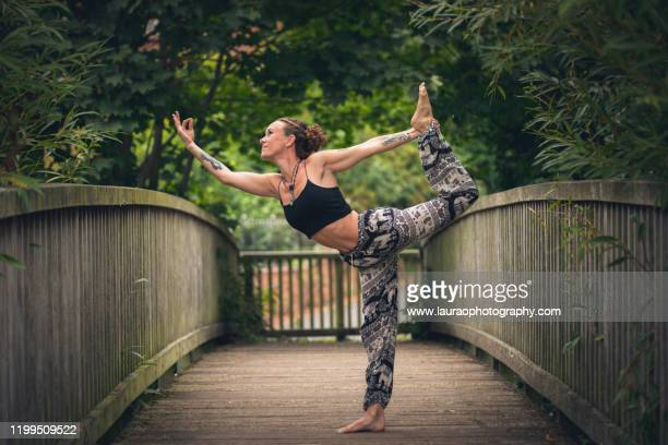 woman outdoors practicing yoga on bridge - milton keynes stock pictures, royalty-free photos & images