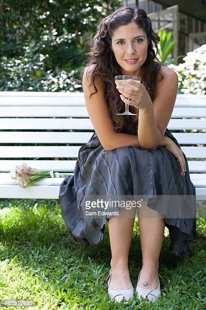Woman outdoors sitting on bench with white wine smiling