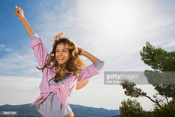 Woman outdoors smiling with arm in the air.
