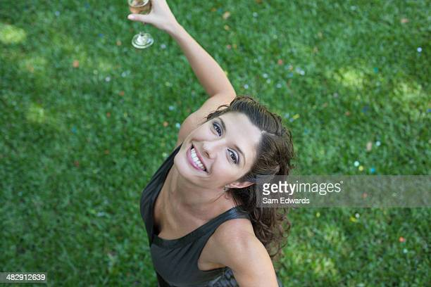 Mulher ao ar livre em pé na grama com champanhe e Confete sorridente