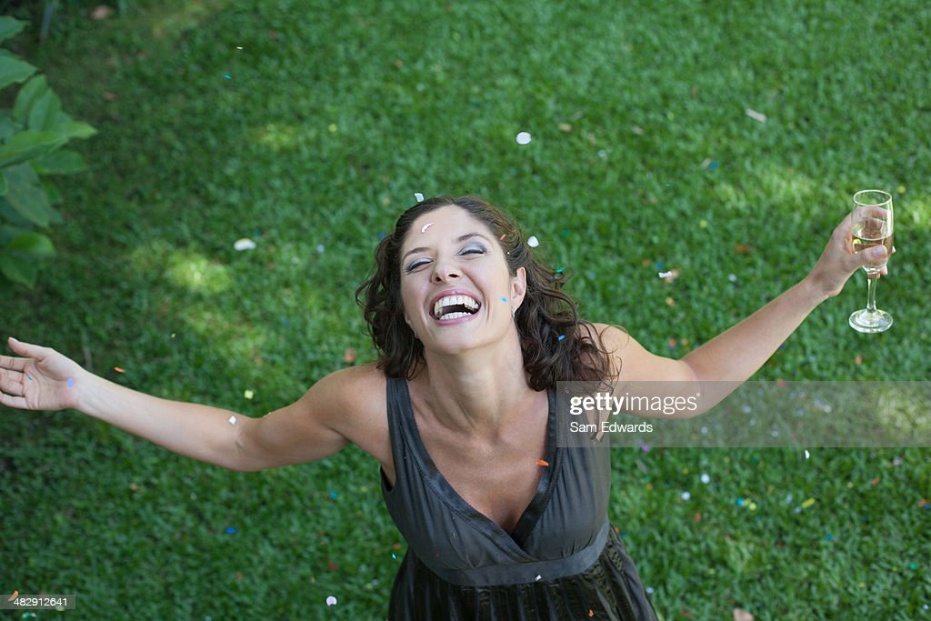 Woman outdoors standing on grass with champagne and confetti smiling : Stock Photo