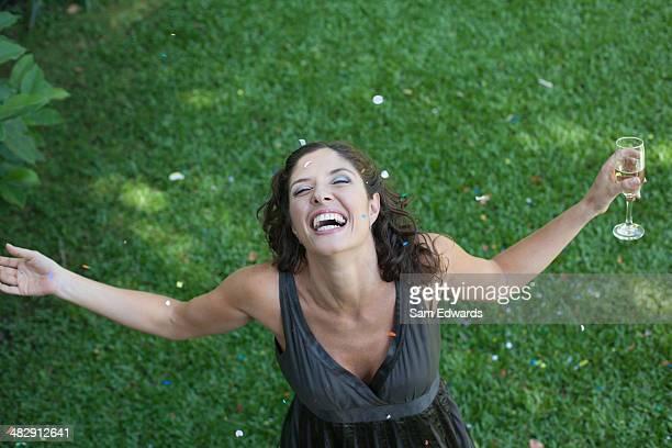 Femme debout à l'extérieur sur l'herbe avec du champagne et des confettis souriant