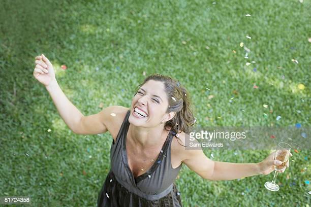 Mulher ao ar livre em pé na grama com champanhe e Confete smi