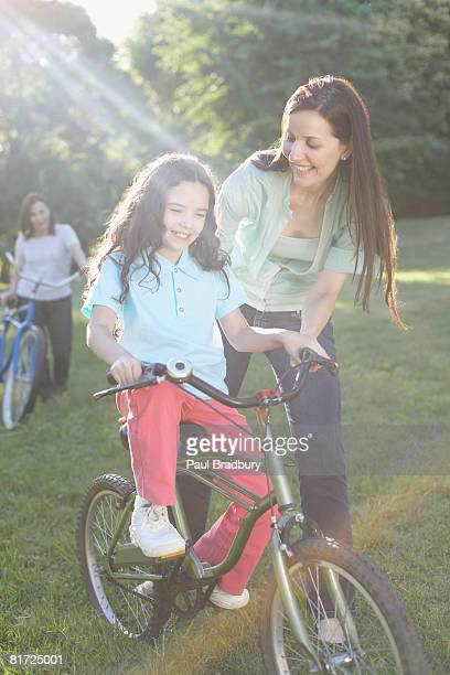 Woman outdoors teaching smiling young girl to ride bicycle