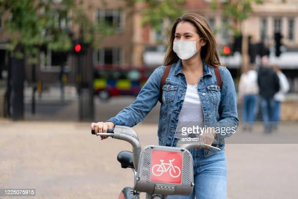 woman outdoors wearing a facemask and renting a bike - riding stock pictures, royalty-free photos & images