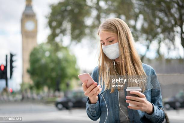 woman outdoors wearing a facemask while using her cell phone and drinking coffee - mobile app stock pictures, royalty-free photos & images