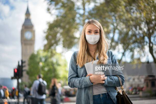 woman outdoors wearing a facemask while walking around london - person in education stock pictures, royalty-free photos & images