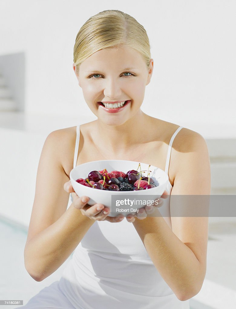 Woman outdoors with bowl of cherries : Stock Photo