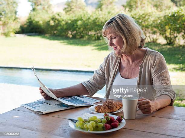 Woman outdoors with breakfast and newspaper