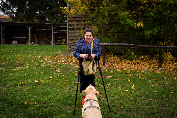 Woman outdoors, with crutches, and dog