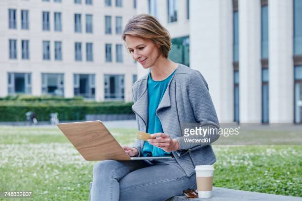 Woman outdoors with laptop, credit card and takeaway coffee