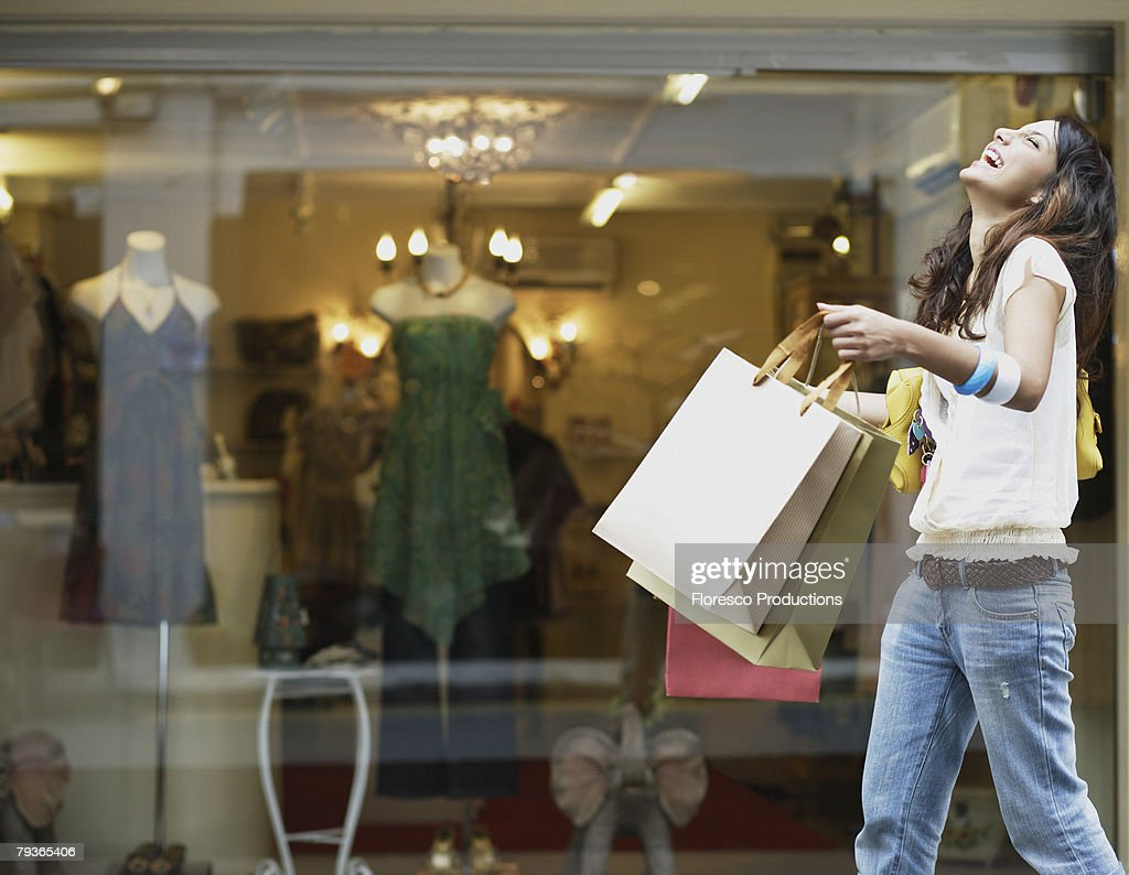 Woman outdoors with shopping bags laughing : Foto de stock