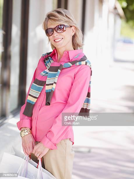 woman outdoors with shopping bags - alleen één oudere vrouw stockfoto's en -beelden