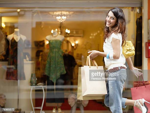 Woman outdoors with shopping bags skipping