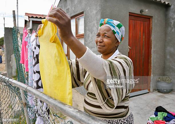 Woman outside her home hanging up washing. Cape Town, South Africa