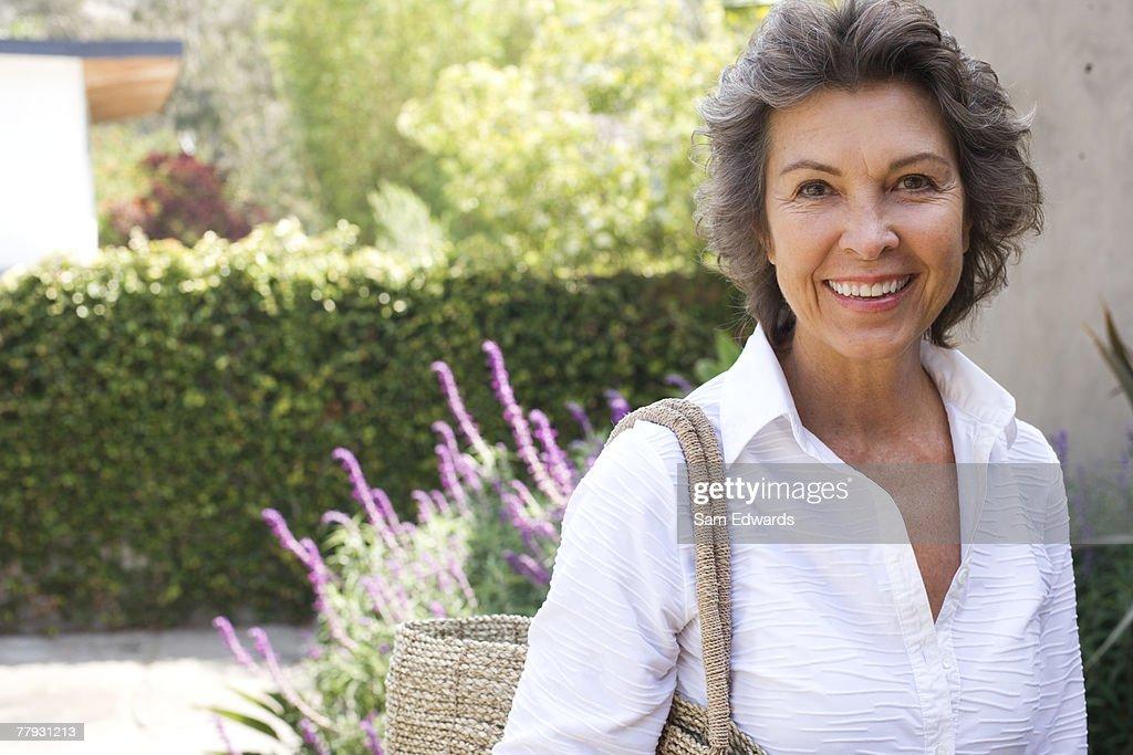 Mulher do lado de fora de casa, com bolsa grande sorriso : Foto de stock