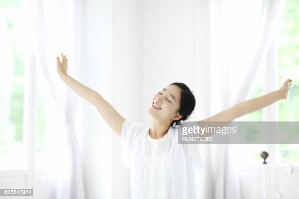 Woman outstretching arms by window