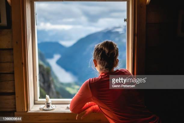 frau mit blick auf fjord in norwegen durch fenster. - wohngebäude innenansicht stock-fotos und bilder
