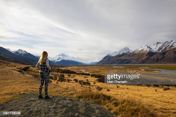 Woman Overlooking Snow Capped Mountains in New Zealand
