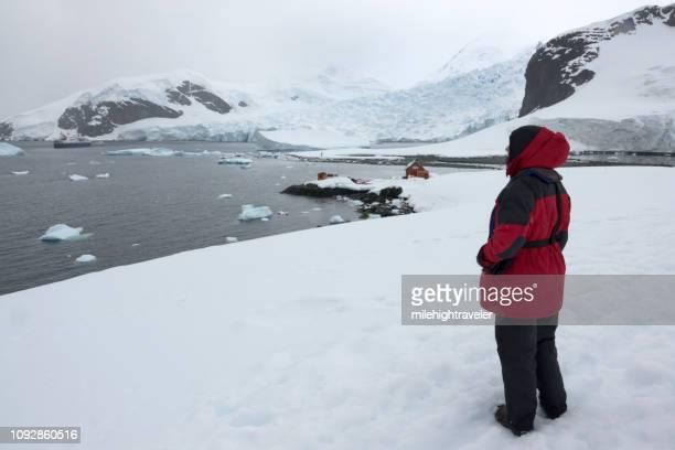 woman overlooks ship almirante brown station danco coast antarctic peninsula paradise bay icebergs - milehightraveler stock pictures, royalty-free photos & images