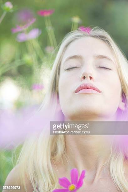 Woman overwhelmed by the sweet fragrence of blooming flowers