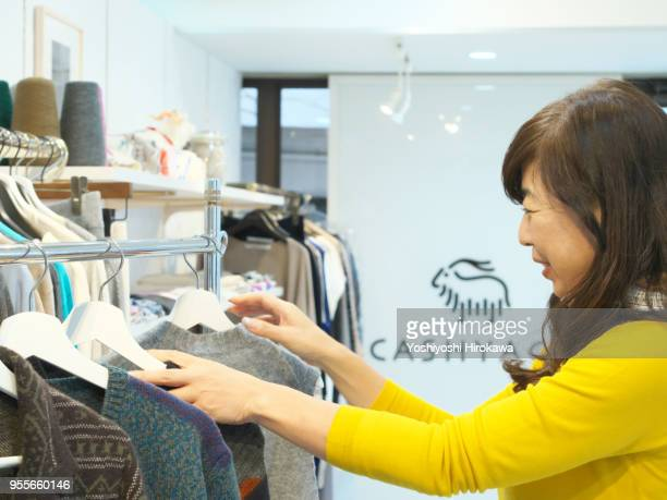 woman owner selects product for customer - far east stock photos and pictures