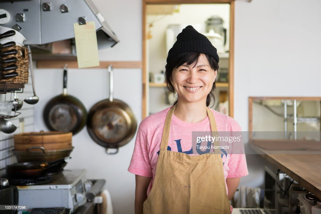 A woman owner who shows a proud smile in the kitchen : Stock-Foto