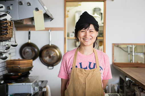 A woman owner who shows a proud smile in the kitchen - gettyimageskorea