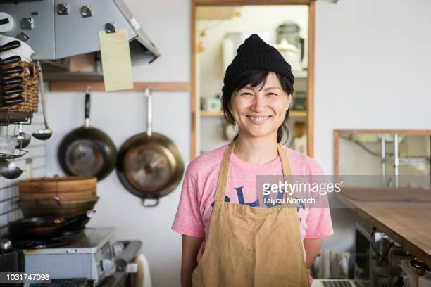 a woman owner who shows a proud smile in the kitchen - smiling stockfoto's en -beelden
