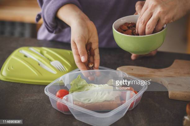 woman packing a healthy school lunch for her daughter - packing stock pictures, royalty-free photos & images