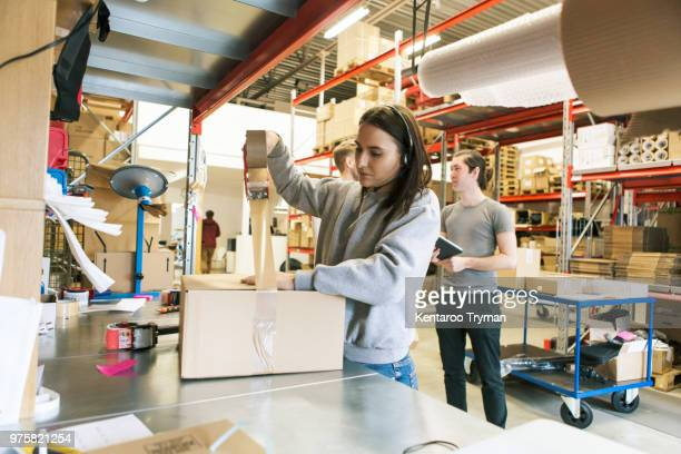 woman packing box while coworkers discussing in distribution warehouse - part time job stock pictures, royalty-free photos & images