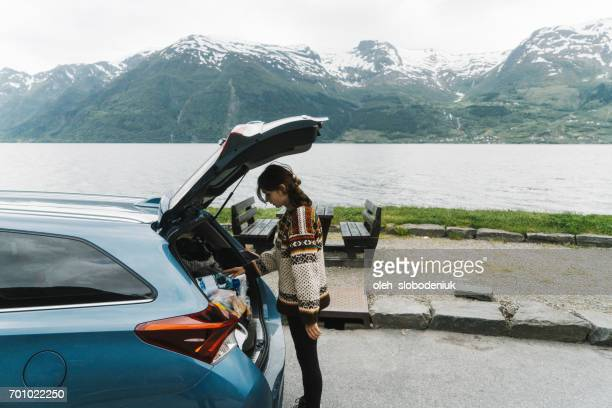 Woman packing car near the fjord in Norway