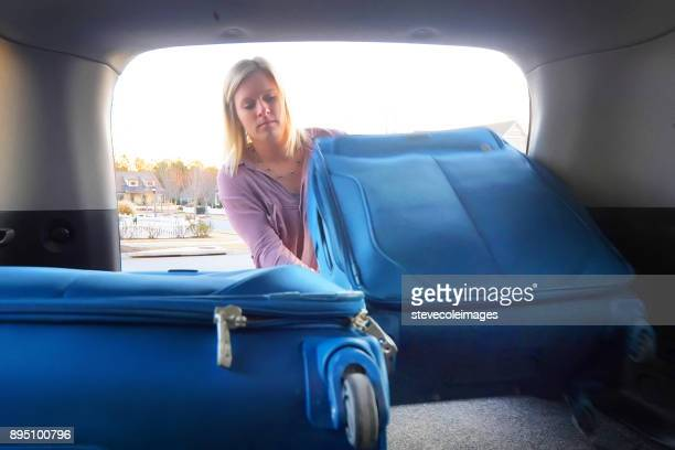 Woman packing car with luggage.