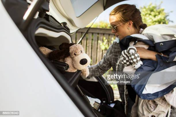 woman packing clothes into car trunk - packing stock pictures, royalty-free photos & images
