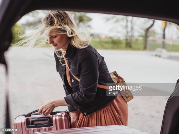 woman packing her car with luggage bags ready for trip - boot stock pictures, royalty-free photos & images