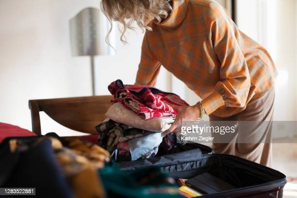 woman packing her suitcase to go on a trip - travel foto e immagini stock